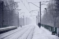 倒空在大雪的火车站与大雾 铁路路轨在雪一场白色雾进来  铁路的概念 免版税库存照片