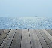 倒空在小船剪影的老木地板与海和天空 免版税库存照片