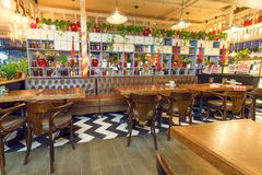 倒空在明亮的咖啡馆里面的舒适室与五颜六色的内部和木桌 免版税图库摄影