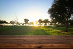 倒空在梦想的乡下日落背景前面的木桌 库存照片