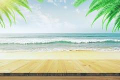 倒空在海滩的木桌与棕榈树 免版税图库摄影