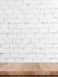 倒空在白色砖墙背景的木桌 免版税库存照片