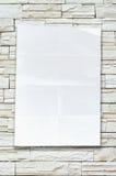 倒空在石墙上的被弄皱的纸张 库存图片