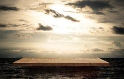 倒空在金黄海洋天空的木展览架 免版税库存图片