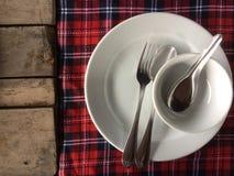 倒空堆白色板材和白色碗在桌布、许多匙子和叉子 库存图片