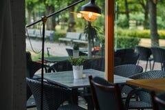 倒空室外咖啡馆-反对绿色公园背景的典雅的黑家具 表和椅子在餐馆大阳台 图库摄影