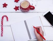 倒空开放笔记本和女性手有一支红色木铅笔的 库存照片
