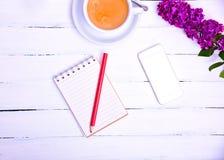 倒空有一支红色铅笔和一个手机的小的笔记本在a 库存图片
