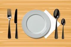 倒空有匙子、刀子和叉子的现实板材在木背景 在木桌上的利器 免版税库存图片
