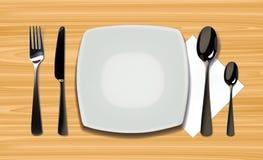 倒空有匙子、刀子和叉子的现实板材在木背景 在木桌上的利器 免版税库存照片