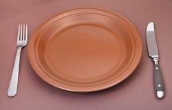 倒空有叉子的陶瓷在褐色的板材和刀子 库存照片
