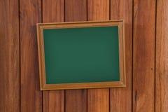 倒空有木制框架的绿色黑板在木墙壁,葡萄酒上 库存图片