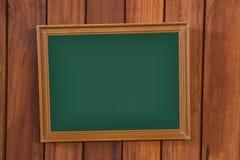 倒空有木制框架的绿色黑板在木墙壁,葡萄酒上 免版税库存照片