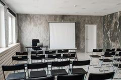 倒空有黑色椅子放映机屏幕的现代教室 免版税库存照片