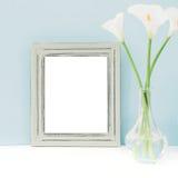 倒空木制框架和花在花瓶在桌上在蓝色背景 嘲笑 库存图片
