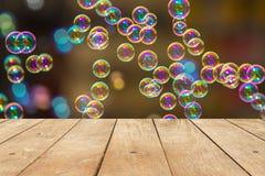 倒空木桌或板条与彩虹肥皂泡bokeh从泡影吹风机在背景 免版税图库摄影