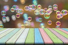 倒空木桌或板条与彩虹肥皂泡bokeh从泡影吹风机在背景 免版税库存图片