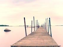 倒空木痣在蓝色湖中水  被聘用的小船和游泳者的老渔码头 免版税库存图片