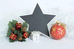 倒空板岩以星的形式写与红色和白色礼物、绿色叶子、杉树冠和一个红色球的一则消息, 库存照片