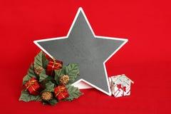 倒空板岩以星的形式写消息在与在冷杉花圈安置的红色和白色礼物的红色背景为 免版税库存图片