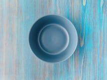 倒空汤的陶瓷碗在老木绿松石桌上 库存图片
