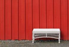 倒空白色塑料被编织的桌在红色木墙壁 免版税库存图片