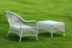 倒空白色塑料被编织的长凳和桌在绿色草坪 免版税库存图片