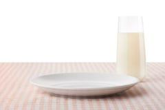 倒空白色板材和杯在方格的桌布的牛奶 免版税库存照片