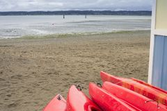倒空租或聘用的红色塑料消遣皮船,存放在沙滩在几小时以后在一个雨天 新月形海滩,萨里, 免版税图库摄影