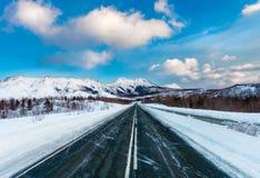 倒空积雪的有白色路标的沥青黑暗的路沿山和小山和蓝天与云彩 免版税图库摄影