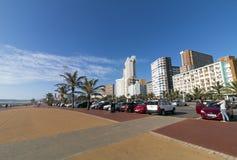 倒空被铺的散步反对沿海海滩前的城市地平线 图库摄影