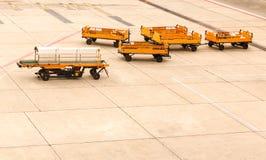 倒空运输行李拖车对在跑道的飞机 免版税库存图片