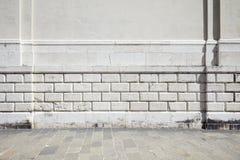 倒空铺磁砖的石边路和白色古老墙壁 免版税库存图片