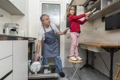 倒空洗碗机的家庭 图库摄影