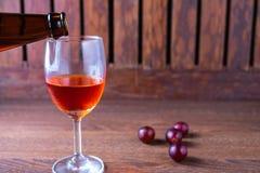倒红葡萄酒入一杯在木背景的酒 免版税库存照片