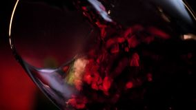 倒红葡萄酒接近的射击到玻璃,黑暗的绯红色背景,浪漫大气,优质录影,日期里 股票视频