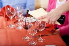 倒红葡萄酒的女服务员 免版税库存图片