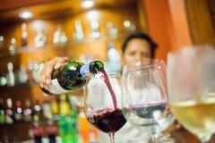 倒红葡萄酒的模糊的人入与白葡萄酒foregroun的玻璃 图库摄影