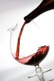 倒红葡萄酒的蒸馏瓶 库存图片