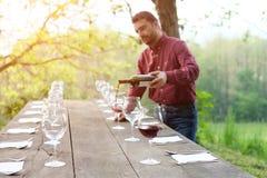 倒红葡萄酒的酒生产商画象 免版税库存照片