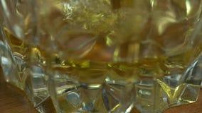 倒苏格兰威士忌酒到与冰的玻璃里 股票录像