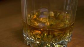 倒苏格兰威士忌酒到与冰的玻璃里 股票视频