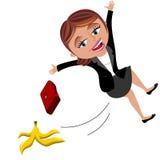 滑倒香蕉果皮的女实业家 免版税库存照片