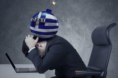 债务炸弹与希腊旗子的在人头 图库摄影