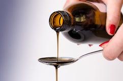 倾倒在匙子之上的瓶液体 在一个空白背景 药房和健康背景 医学 咳嗽和冷的药物 免版税库存照片