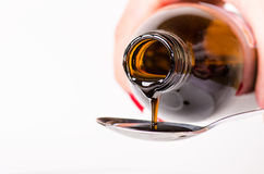 倾倒在匙子之上的瓶液体 背景查出的白色 药房和健康背景 医学 咳嗽和冷的药物 免版税库存照片