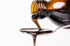 倾倒在匙子之上的瓶液体 背景查出的白色 药房和健康背景 医学 咳嗽和冷的药物 库存图片