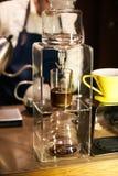 倾倒在咖啡玻璃器皿之上的专业barista热水 库存照片