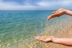 倾倒在海背景之上的女性手珊瑚沙子 库存图片