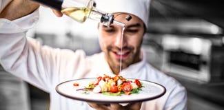 倾倒在膳食之上的英俊的厨师橄榄油 免版税图库摄影